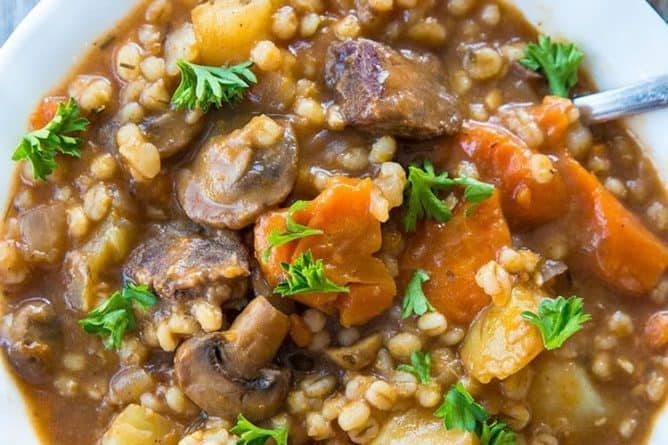 close up Beef & Barley Stew in a white bowl with spoon