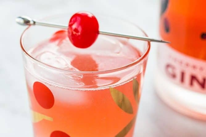 Gin Rickey Cocktail in Collins glass with ice cubes garnish with cherry on pick