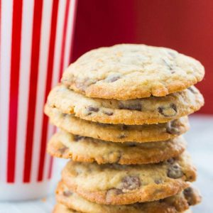 Close up Stack of DoubleTree Hotel Chocolate Chip Cookies, tall stripe red tumbler at the back