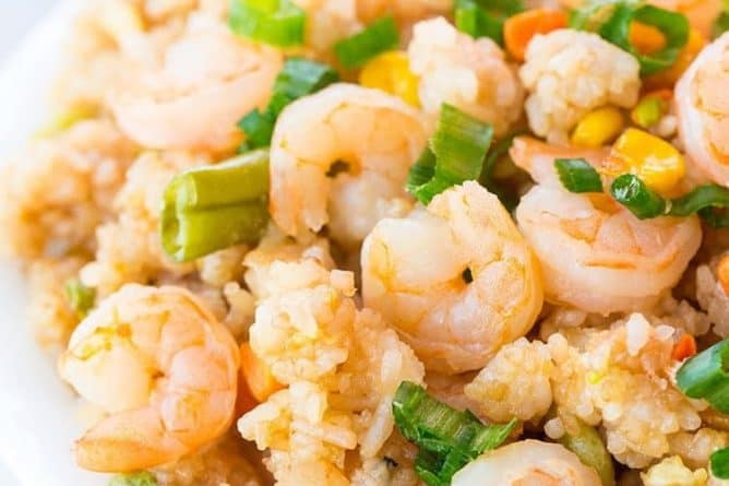 Shrimp Fried Rice in a white bowl topped with chopped green onions