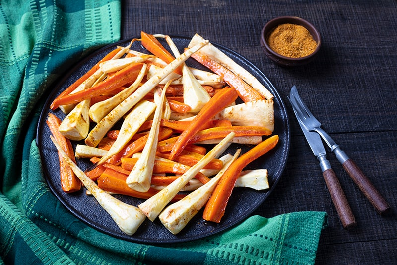 green tablecloth underneath a black serving plate with roasted parsnips and carrots, Cajun seasoning bread knife and fork on its side