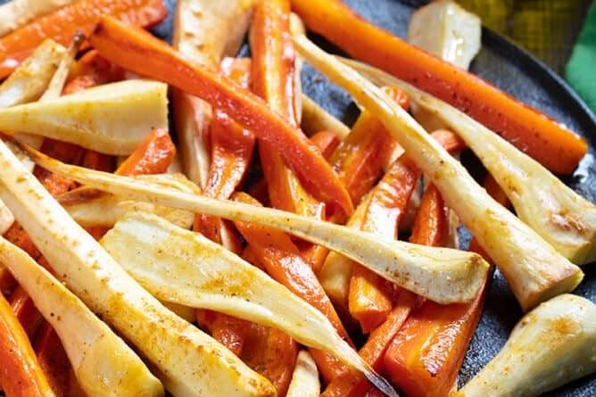 close up black serving plate with roasted parsnips and carrots, Cajun seasoning, olive oil, bread knife and fork on its side
