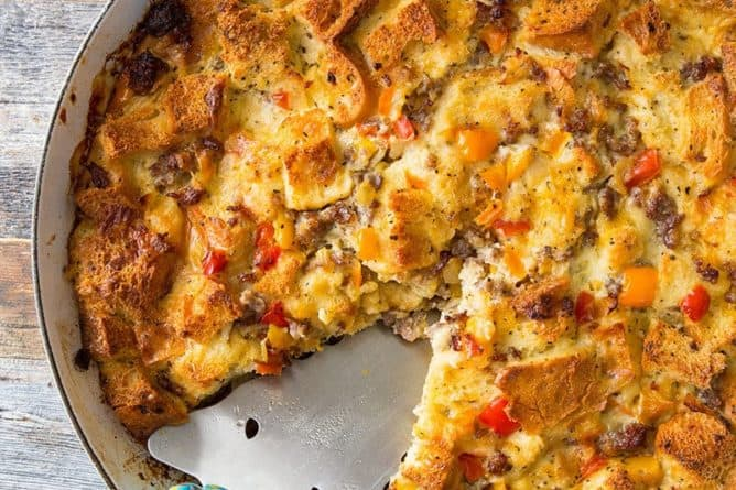 close up Sausage & Peppers Overnight Breakfast Strata in a pan on wood background