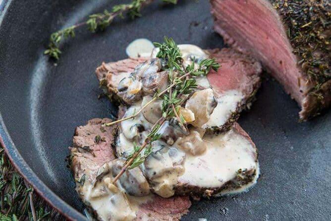 Sliced Tenderloin Roast au Poivre & Mushroom in Red Skillet with Cognac Mushroom Sauce