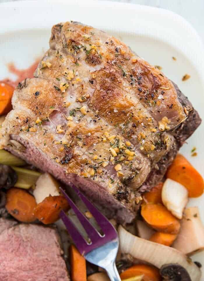 Top down Sliced Slow Cooker Striploin Roast Beef Served with Vegetables and Gravy