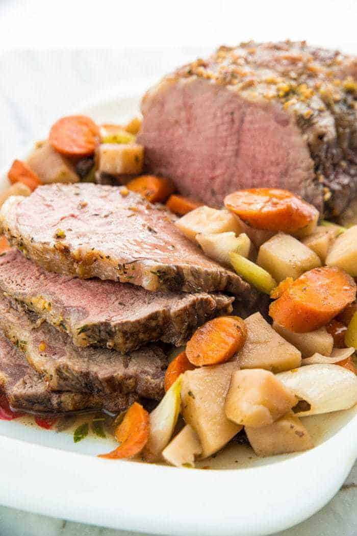 Close up of Sliced Slow Cooker Red Wine Striploin Roast Beef Served with Vegetables and Gravy