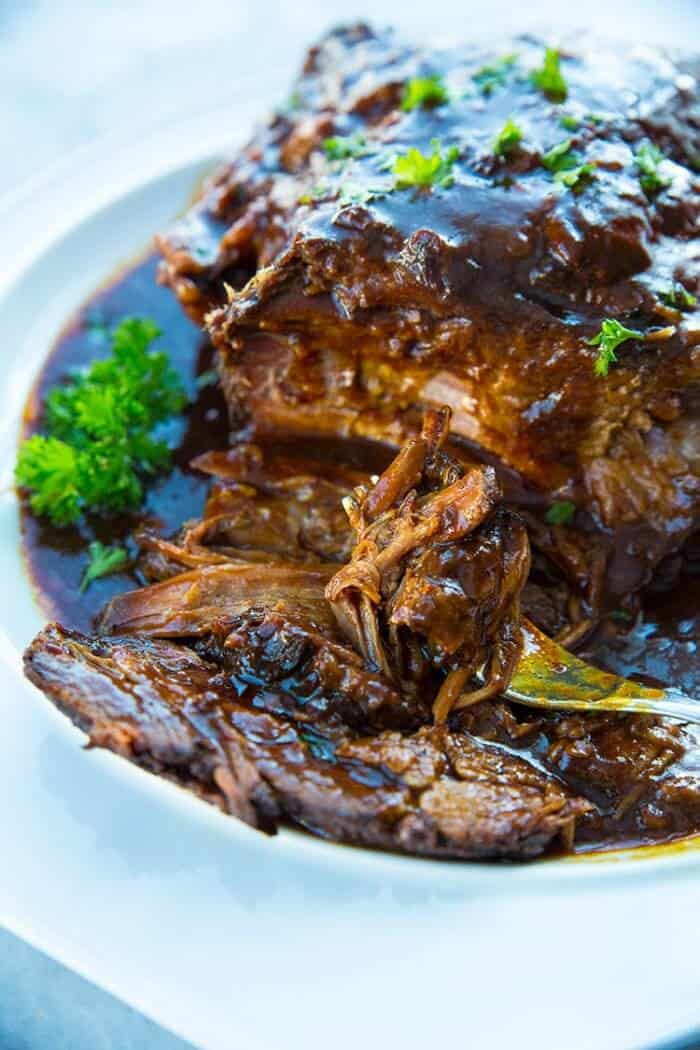 Slow Cooker Brisket in a white plate with root beer and BBQ sauce