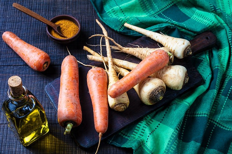Parsnips and Carrots on a wooden cutting board with green tablecloth underneath, olive oil and cajun seasoning on its side