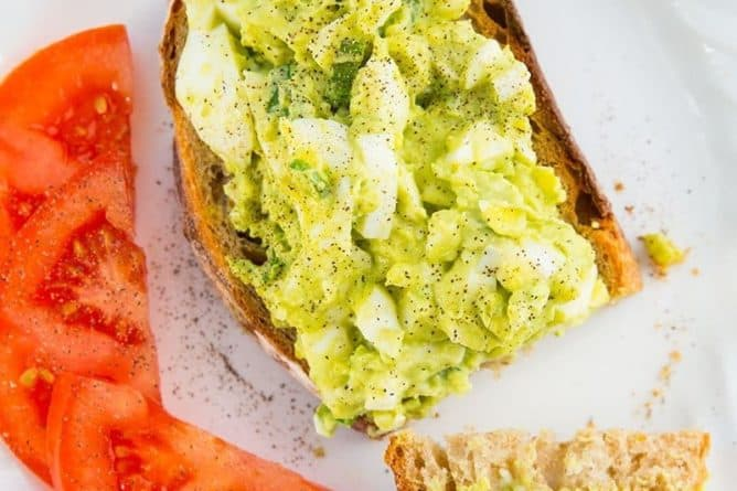 white plate with slices of red tomatoes and open faced toasted bread topped with Avocado Egg Salad