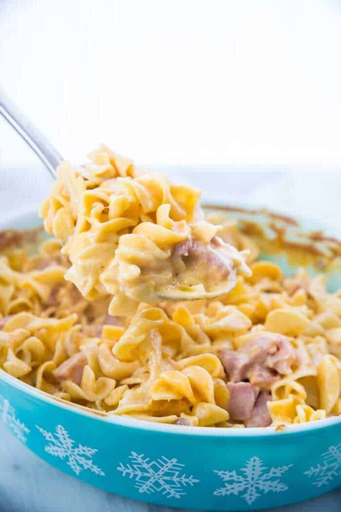 Ham & Noodle Casserole being spooned out of a casserole dish