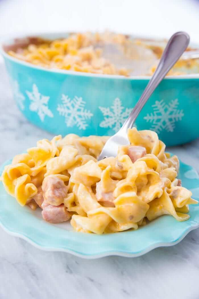 Creamy ham & noodle casserole on a vintage Hazel Atlas ruffled turquoise plate with a fork