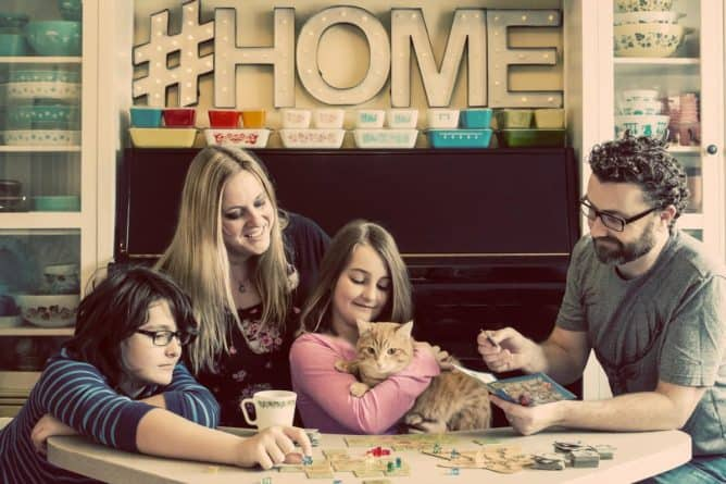 Whole family relaxing and enjoying the time with one another together with their cat. All kitchenware on the background