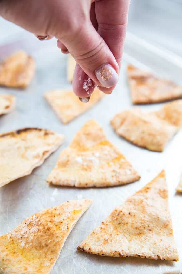 Homemade Pita Chips Being Sprinkled With Flaked Sea Salt