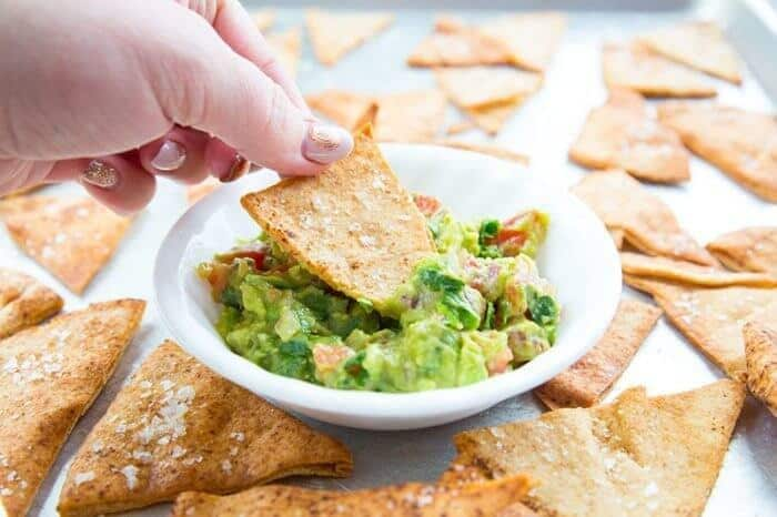 Dipping the Homemade Pita Chips into dipping dish with tomatoes, garlic, cilantro, onions and avocado