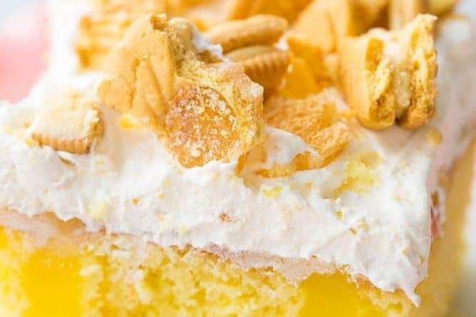 Close up Slice of Lemon Better Than Sex Cake Topped with Whipped Cream and Crushed Lemon Cookies in Ruffle Plate