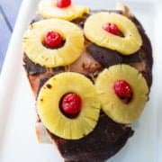 close up Slow Cooker Ham on a vintage Corelle Serving Platter with pineapple rings and cherries on top