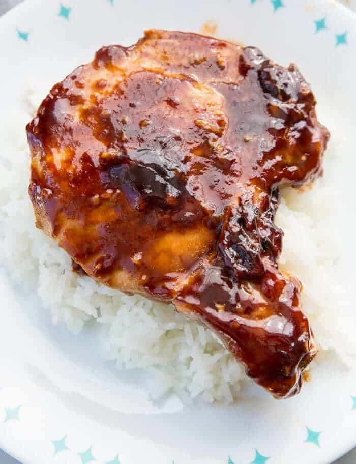 Close up of a sauce covered pork chop on white rice