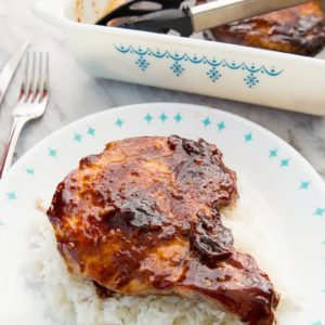 close up of Saucy Baked Pork Chops on a bed of rice on a blue and white plate