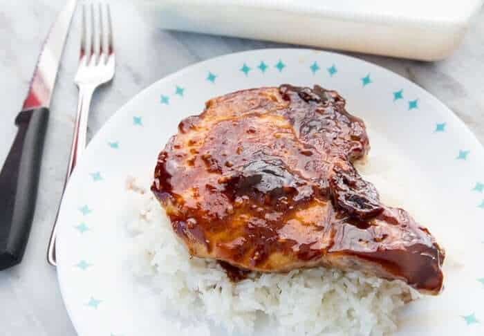 Saucy Baked Pork Chops on a bed of rice on a blue and white plate
