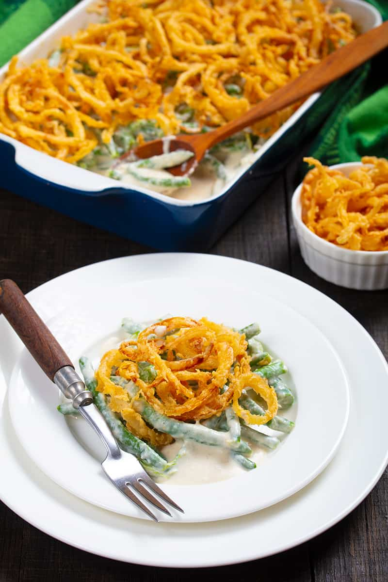 Asparagus green bean casserole serving in a small white plate with fork, whole casserole of green bean with asparagus in the background
