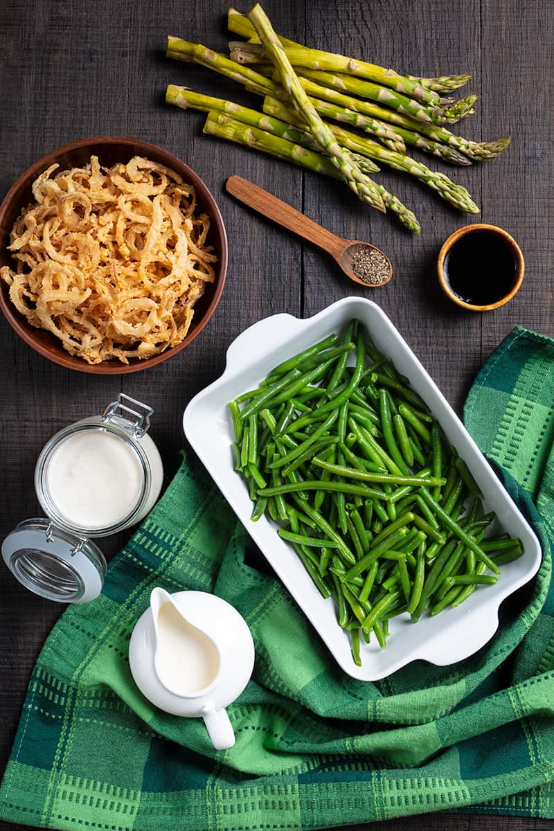 Asparagus Green Bean Casserole ingredients in wood background with green tablecloth