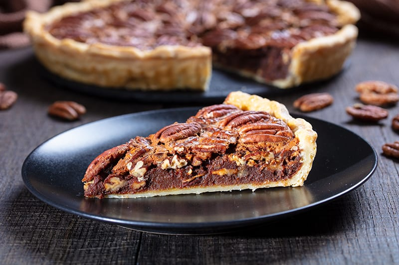 a slice of Chocolate Pecan Pie on a black medium serving plate and the remaining part of the pie on its background