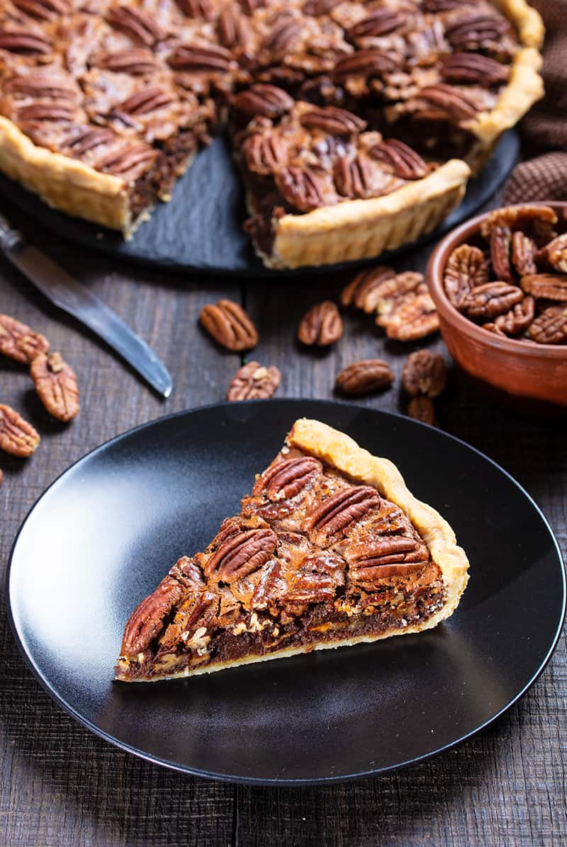 a slice of Chocolate Pecan Pie on a black medium serving plate, a cup of pecans and the remaining part of the pie on its background