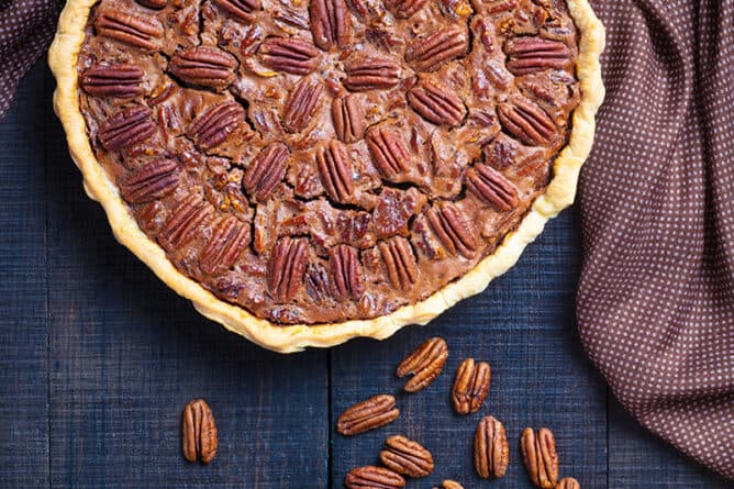 brown polka dot tablecloth on dark wood background, whole Chocolate Pecan Pie with a cup of whole pecan and a cup of chocolate chips beside it