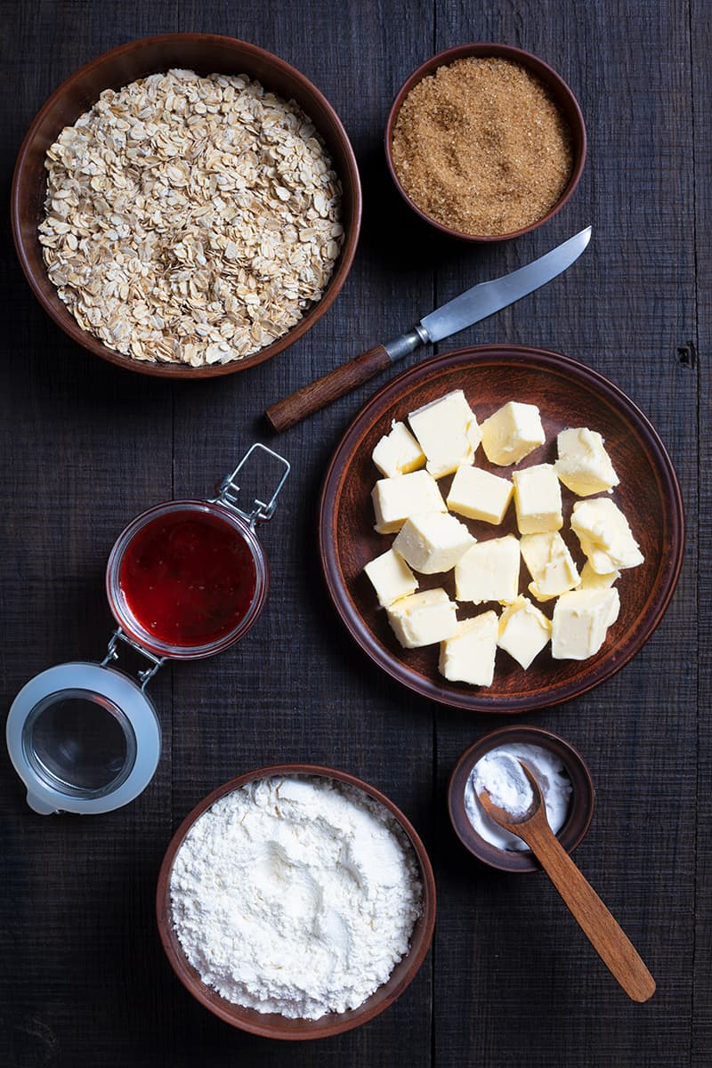 ingredients for cranberry oatmeal bar cookies in a dark wood background