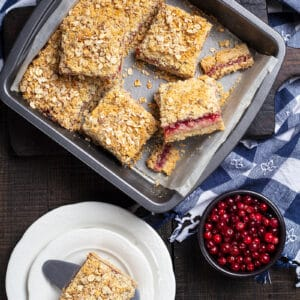 blue checkered tablecloth underneath a baking pan lined with parchment paper with Cranberry Oatmeal Bars, cranberries and white plate with a piece of Cranberry Oatmeal Bar on its side