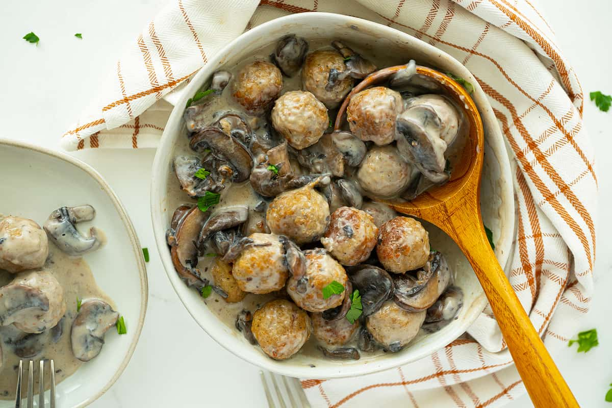Meatballs with Homemade Mushroom Sauce on a plate with wooden spoon