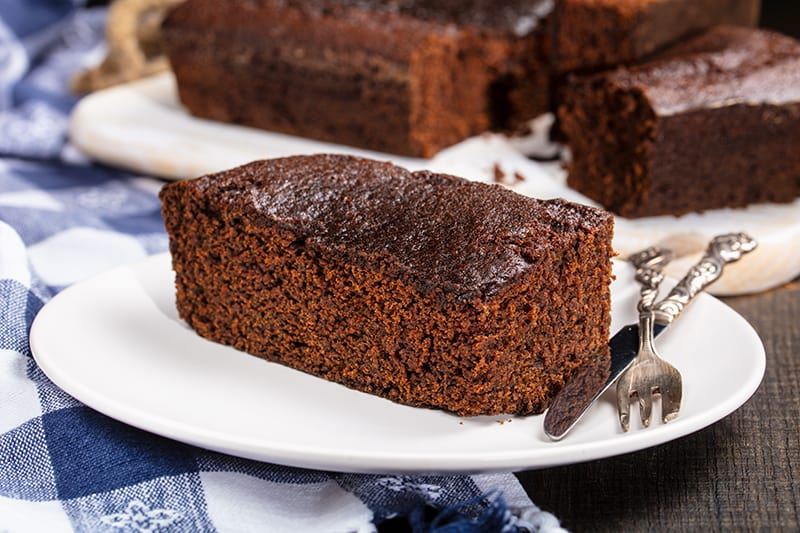 slices of Old Fashioned Gingerbread on white plates with fork and bread knife