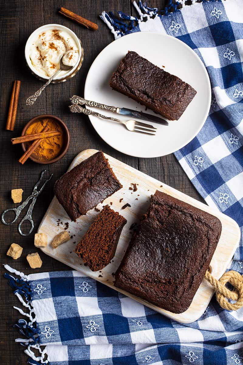 Old Fashioned Gingerbread slices on wooden cutting board and white plate with fork and bread knife