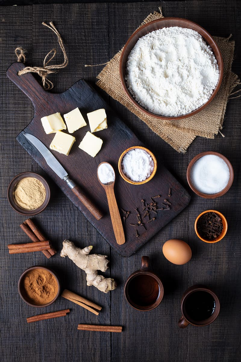 Old Fashioned Gingerbread ingredients in a wooden cutting board on a dark wood background