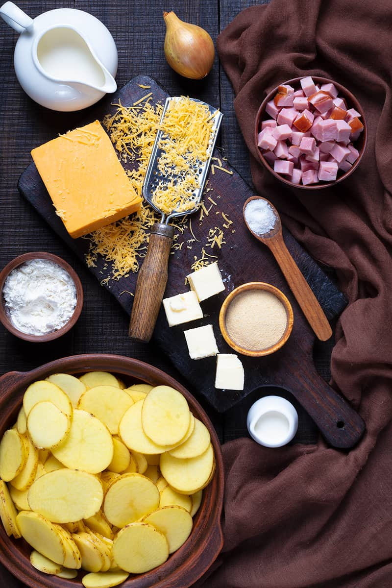 ingredients for Scalloped Potatoes and Ham on wooden cutting board, brown tablecloth and wood background