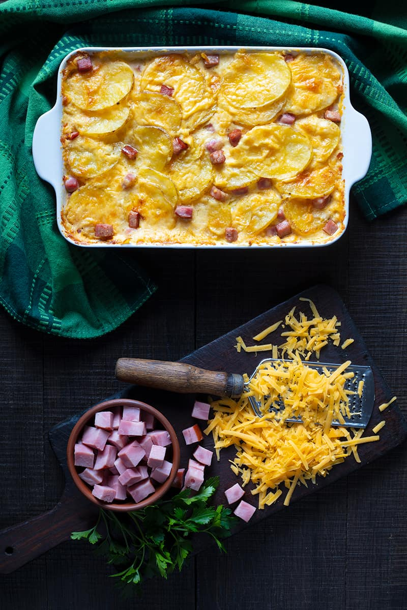 Scalloped Potatoes and Ham in a white casserole dish with green tablecloth underneath, ingredients in a wooden cutting board beside it