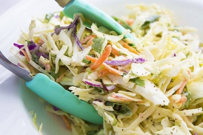 Dishing up homemade coleslaw with turquoise tongs