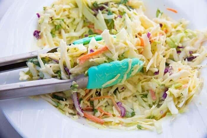 Kitchen tongs on Classic Homemade Coleslaw in a white plate