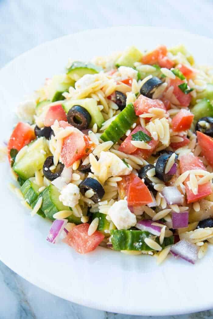 Greek Orzo Salad close up of tomatoes, orzo, black olives feta and purple onions in a white bowl