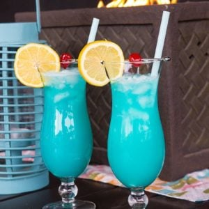 Close up of Two Blue Lagoon Cocktails with lemon slice and cherry