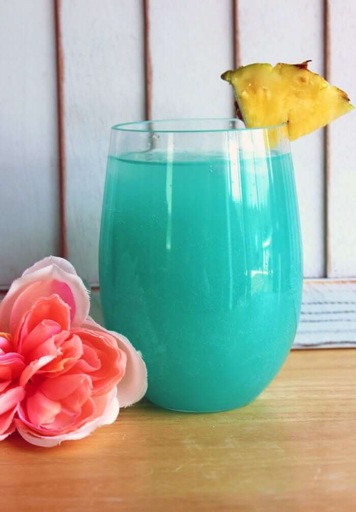 Blue Hawaiian Cocktail in a Hurricane Glass with a slice of pineapple