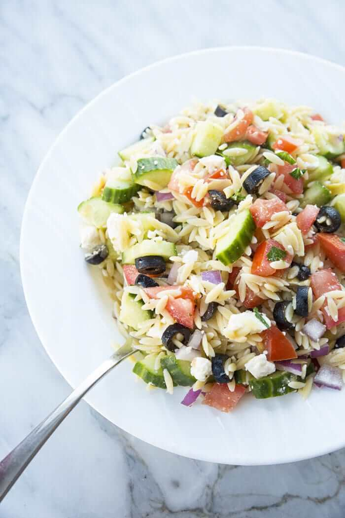 Greek Orzo Salad- tomatoes, orzo, black olives feta and purple onions in a white bowl