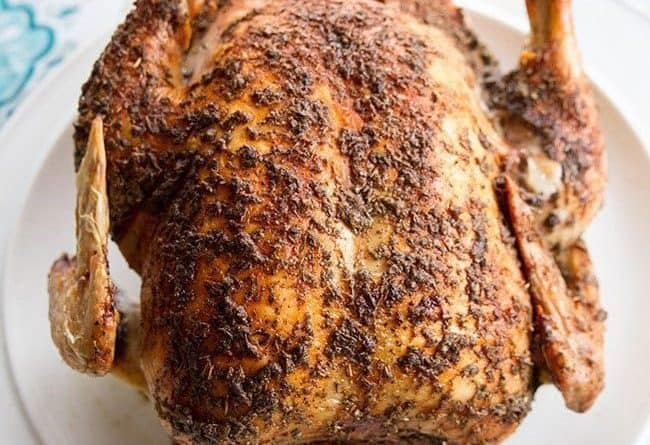 Close up of a whole roast chicken on a white plate