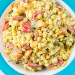 Top down shot of Corn Salad with Green Chile Dressing in a blue Pyrex Bowl