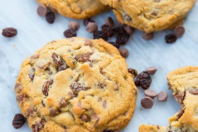 Close up of Milk Chocolate Chip Cookies with Raisins on white marble slab