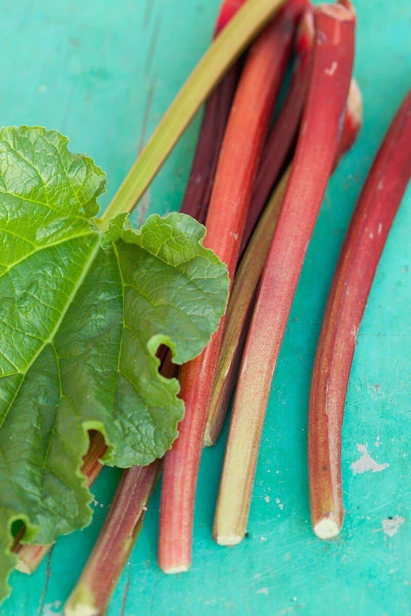 cut rhubarb stalks on a turquoise wooden board
