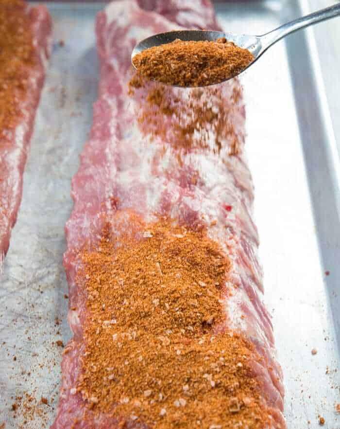 Sprinkling dry rib rub on top of raw pork ribs