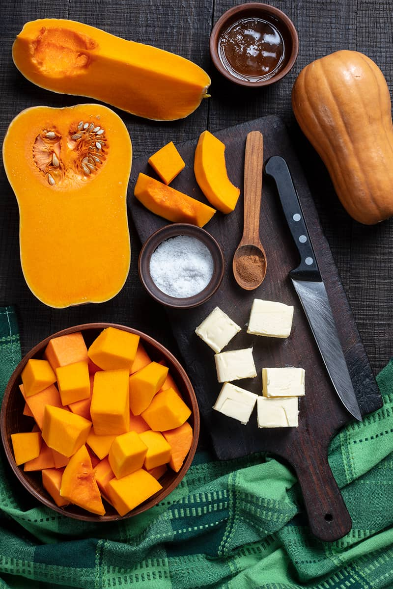 Honey & Cinnamon Roasted Butternut Squash ingredients on wooden chopping board with knife and wooden spoon