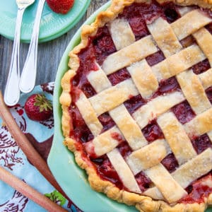 Strawberry Rhubarb Pie in a baking dish, serving plates with fork and fresh strawberry on the side