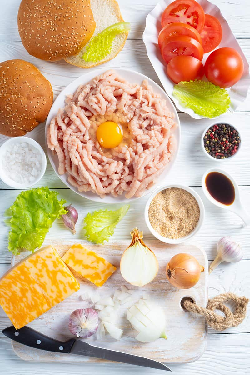 top down shot of all the ingredients needed in making Turkey Burgers in a white background